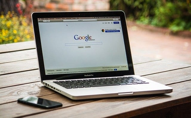 A laptop with Google Search page on its screen